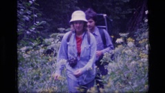 1973: a young man and a women walking in the middle of flower plants SCAPEGOAT Stock Footage
