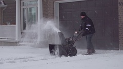 A wide-shot of a man using a snow-blower on his driveway in the suburbs. Stock Footage