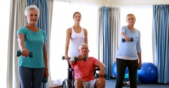 Trainer assisting senior citizens in performing exercise Stock Footage