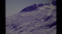 1975: mountain peaks with a little snow; people backpacking in rocky area Stock Footage