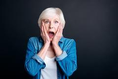 Pleasant elderly woman expressing wonder Stock Photos