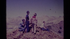 1975: people on a ridge with a stack of rocks and a man pointing out  Stock Footage