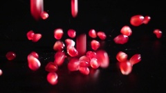Falling seeds of pomegranate on black background, slow motion Stock Footage
