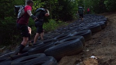 Adventure race athletes going through tire obstacle up hill Stock Footage