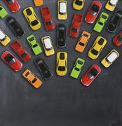 Traffic jam concept with multiple toy cars on a blackboard Stock Photos