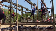 Athletes climbing monkey bars at adventure obstacle race Stock Footage