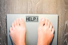 Help to lose kilograms with woman feet stepping on a weight scale Stock Photos