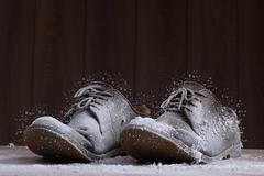 Frozen brown suede shoes with brown laces. Stock Photos