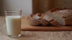 Glass of milk and sliced bread on kitchen table. Dairy product at breakfast Stock Footage