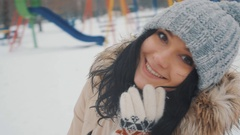 Beautiful young girl with a knitted cap and gloves in winter park Stock Footage