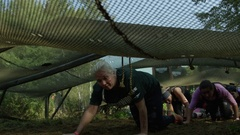 Athletes crawling under obstacle in fitness race Stock Footage