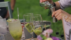 Bartender makes fruity alcoholic cocktails on wedding party outdoors Stock Footage