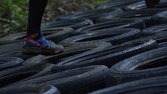 Athletes racing through obstacles and tires in fitness competition Stock Footage