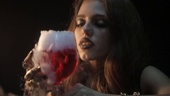 Girl with mysterious make-up and jewelry on the hands smelling the aroma of wine Stock Footage