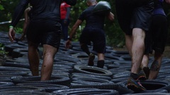 Close up group of people walking through tire obstacle course race Stock Footage