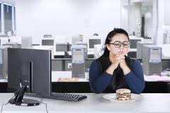 Overweight businesswoman hesitates eat burger at home Stock Photos