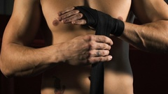 Man boxer pulls the bandages on his hands in slowmotion Stock Footage