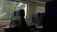 People entertaining with cell and laptop in train Stock Footage