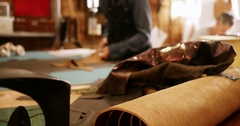 Craftswoman cutting leather with scissors Stock Footage
