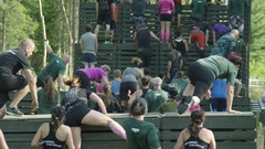 Enormous group of athletes racing over obstacles in fitness challenge Stock Footage