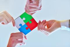 Business people group assembling jigsaw puzzle and represent team support Stock Photos