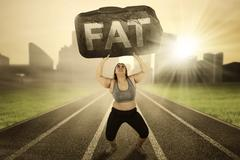 Overweight woman with burden on track Stock Photos