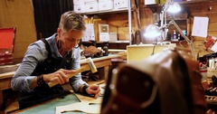 Attentive craftswoman nailing leather Stock Footage