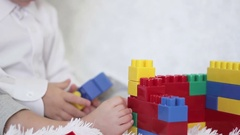 Boy builds a house out of colored blocks Legosidya on the couch Stock Footage