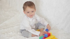 Boy child sitting on the couch playing with toys and laughs. Stock Footage