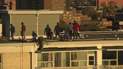 Maintenance workers working on top of a high-rise building  Stock Footage
