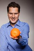Diet and healthy nutrition. Man recommending orange Stock Photos