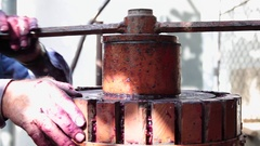Old man using a wine press to crash grapes for wine production Stock Footage