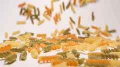 SLOW MOTION: Stream of multi colored fusilli pasta moving to a camera Stock Footage
