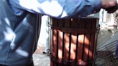 Vintner turning wine press with grapes in it Stock Footage