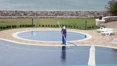 Pool guy cleaning outdoor swimming pool with a vacuum tool Stock Footage