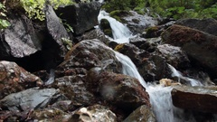Close up of water falling between rocks at mountain stream Stock Footage