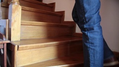 Young man's legs climbing wooden stairs in an old house Stock Footage