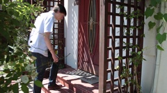 Young man getting house key from under the welcome mat and opening the door Stock Footage