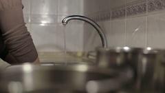 Beautiful young housewife washing the dishes. Dish-washing. Stock Footage