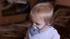 Child holds a mask vapor inhaler. Breathing through a steam nebulizer. Stock Footage