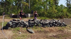 Women effortlessly running through obstacle race Stock Footage