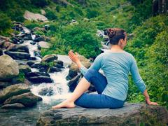 Woman doing Ardha matsyendrasana asana outdoors Stock Photos