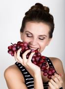 Young smiling woman holding fresh red bunch of grapes Stock Photos