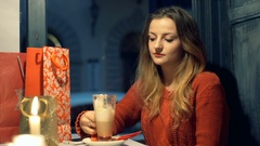 Girl drinking coffee in the cafe and doing serios look to the camera  Stock Footage