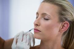 Female patient receiving a botox injection on face Stock Photos