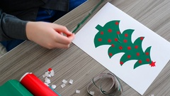 Teen Boy making Christmas card from colored self-adhesive papers Stock Footage