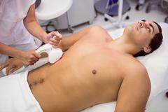 Man receiving laser hair removal treatment Stock Photos