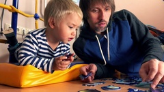 Father and his little blond son assembling puzzle together. Man and his kid Stock Footage
