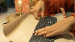 Girl wrapping tie in a festive paper and puts gold band on it Stock Footage