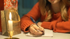 Girl sitting by the table in the cafe and write wish list to Santa Claus Stock Footage